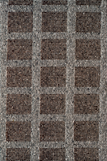 A gray-toned quare grid enclosing tan squares. pattern achieved by color alternations of A & B warps and wefts in plain weave (commonly called Log Cabin) and a change of one color. The pattern effect is heightened by the increased thickness of alternate wefts.