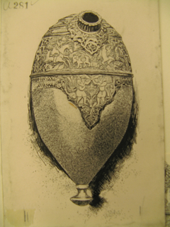 An ovoid-shaped vessel, probably a flask of some sort, with a small opening at the top.  The upper portion has bands of carving with figure and animal motifs.