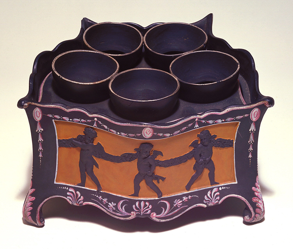 Four-sided, serpentine sides, front longer than back; shaped edges, scrolled feet.  Cover set on angle, with five cups for bulbs and two piercings.  Relief panels in front and two sides, with putti bearing garland, against orange field; borders filled with floral forms in pink and white, inside glazed.