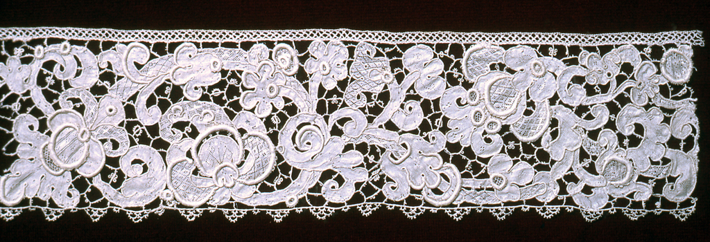 Border of Gros Point de Venise with curvilinear forms in a floral and foliated design. Pattern outlined by cordonnet and connected by brides picotées and interspersed by portes and gaze quadrillée.