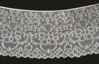 Lille-style bobbin lace flounce with an allover symmetrical design on a net ground in a design of angular curves, garlands and swags. Flounce has been set into a silk tape at top.
