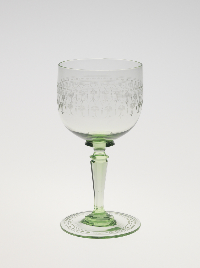 Mouth-blown crystal wine glass, partly facet-cut and polished in green, with a dainty floral engraved border.