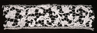 Border fragment of Gros Point de Venise in a large floral and foliated serpertine design. Pattern outlined by cordonnet and connected by brides picotées and interspersed by portes and gaze quadrillée.