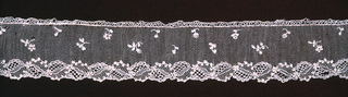 Border of Point d'Alençon with a design of small-scale floral shapes edged by a garland on one side.
