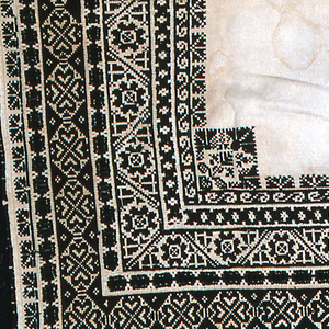 Rectangle of undyed cloth with a wide border of black wool lace on three sides and deep border of floral bands in black silk cross stitch with guard bands of black and white cutwork.