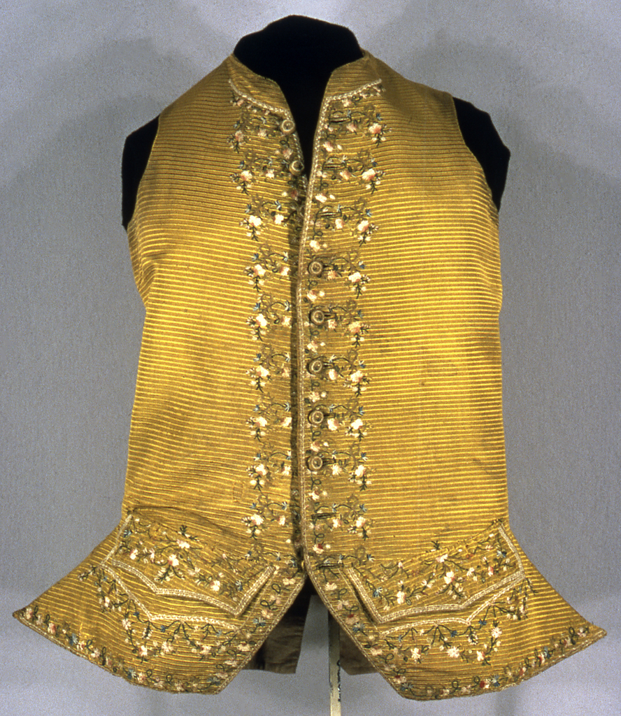 Gentleman's waistcoat in dark golden color has horizontal ribbing and embroidery in multicolored silks in a design of floral sprays and vines. Waistcoat is in a cutaway style with shaped pocket and a small standing collar.