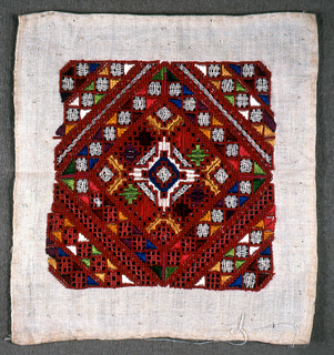 Unfinished sampler with a square of diamond-shaped pattern in reds, orange, yellow, green and blue.