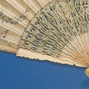 Pleated fan with a painted parchment leaf with three cartouches: the center shows an interior with a man and two women playing music and dancing; the two side cartouches show butterflies and shells. Scattered insects on the reverse, with a floral border. Twenty-four ivory sticks which are carved, pierced, painted and gilt, with amorini, fruit and flower chains, and with red foil inserted in the guard sticks. Embroidered case with red lining, removable lid.