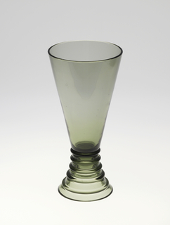 Mouth-blown green glass with glass applications. Tall vase with ring-shaped base.