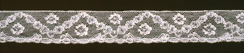 Border of Lille-style lace edged with a garland formed by floral blossoms in a serpentine arrangement.