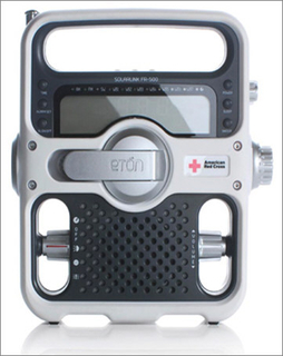 Red and gray rectangular form with rounded corners and edges; horizontal opening at top for handle; telescoping antenna on left; function and control words on plastic face. At center, silver-colored folding hand crank, American Red Cross logo on right' pierced speaker below with volume and power control knobs on left and right; additiona control knobs on right side.