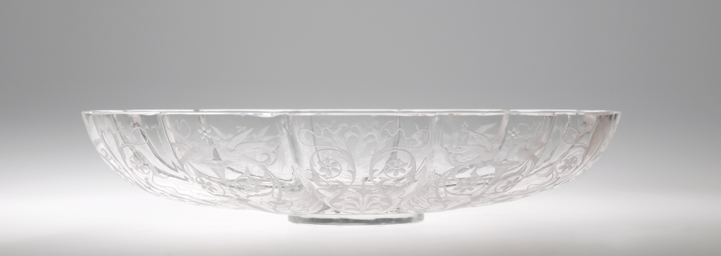 Engraved with delicate foliate design, featuring stylized flowers and birds and a scalloped edge of plate.