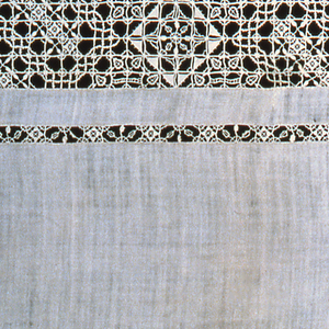 Tablecloth edged by lace triangles. Cloth is divided into bands of insertion and solid cloth. Insertions are small-scale squares of reticella.
