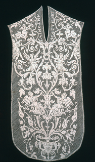 """Front and back panels for a chasuble in a similar design. On front panel, the names """"Antonius"""" and """"Matthaei,"""" while the back panel has an image of Saint Barbara holding an architectural structure in her right hand and a palm leaf in her left. There are areas of identically composed design on both panels with pairs of winged putti and angels set within a large-scale arrangement, emerging from an urn of floral and foliated scroll pattern, surrounding a large medallion which contains a floral spray."""