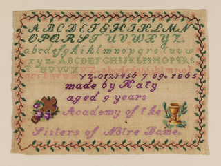 Four alphabets, one set of numerals, date and inscription flanked by a cross and chalice, with a floral vine border. The inscription reads:  made by Katy aged 9 years Academy of the Sisters of Notre Dame