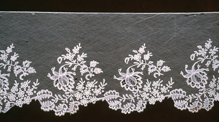 Band of Point d'Angleterre with a scalloped border of elaborate floral sprays along one edge. Fond: Droschel.