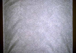 Horizontal zigzag of irregular silver dots on a silver-grey background.