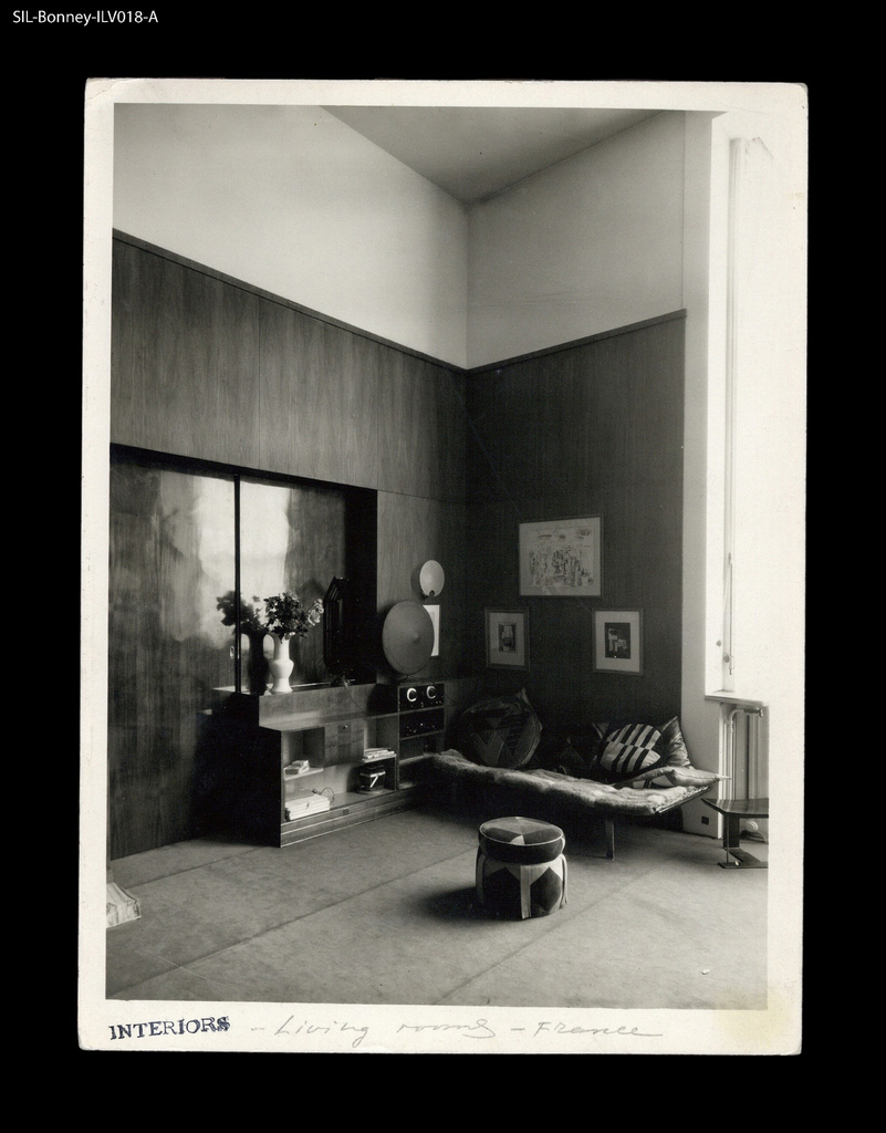 Interior — living room. Neuilly (today Paris), France, 1927-28.  Domicile of Jacques Heim, 17, avenue de Madrid, Neuilly-sur-Seine.  Two-floor space.  Walls, sliding doors, cupboards, fireplace, and radio cabinet in varnished walnut.  Stairs in marble.  Gabriel Guévrékian (1900-70), architect, with Ernest Denis (1849-1921).