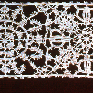 Border of squares filled with floral blossoms. Filling stitches: bars decorated with picots, small openings in the solidly-worked areas of the lace.