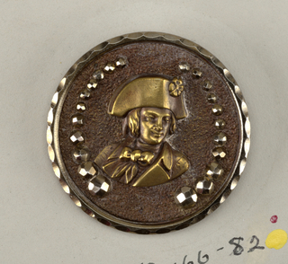 "Circular button with bust of woman (?) in helmet and armor; ""PAX"" under figure, within band around rim.  On card 43"