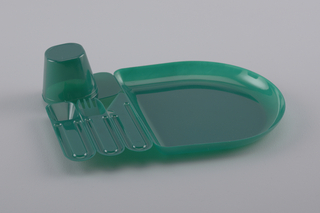 Dark green molded plastic unit comprising joined elements of an individual 'place setting':  cup with tab handle (inverted), spoon, fork, knife and D-shaped plate; elements can be separated at joins. Disposable
