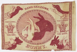 "Rectangular panel of cream-colored cotton printed in red. The design shows various shadow figures made with the hands. In a large central oval frame, a pair of hands making the shadow of a rabbit, titled below ""Bunny."" In the four corners are hands and shadows forming ""The Camel,"" ""The Dog,"" ""The Goose,"" and ""The Goat."" To the left and right of the central oval, the crest of the Prince of Wales – three plumes in a crown – and the legend ""Ich Dien"" (""I Serve""). The configurations are similar to those found in Henry Bursill's ""Hand Shadows to Be Thrown Upon the Wall,"" 1859."