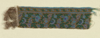 Close-set horizontal repeat of flowering sprays. Flower and leaf guard band at bottom with decorated guard strips. In purples, bright turqoise and green on a dark tan ground. Long warp fringes on one end separated by narrow band of coarse cotton wefts.