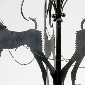 Cut steel and wrought iron chandelier with a triad of gazelles grazing on the branches of the tree-like central rod with collars connecting each by leashes. Each animal stands behind a candle holder set on a circular disks surrounded by a jagged wolf-tooth pattern, while various tendrils spring from the sculptural fixture.
