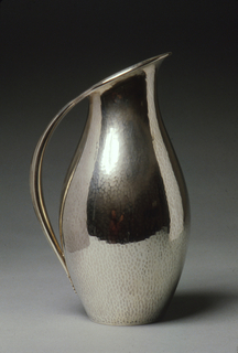 Ovoid silver pitcher with stippled texture; spout rises asymmetrically from the volume while its lip is pitched at an angle and continued by a sleek curving handle.