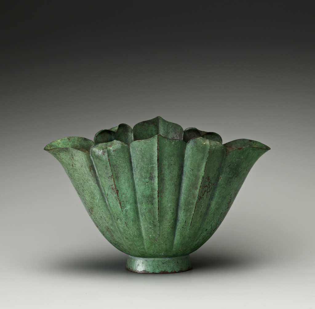 Patinated copper vase with stylized cabbage-leaf-like body atop a circular foot.