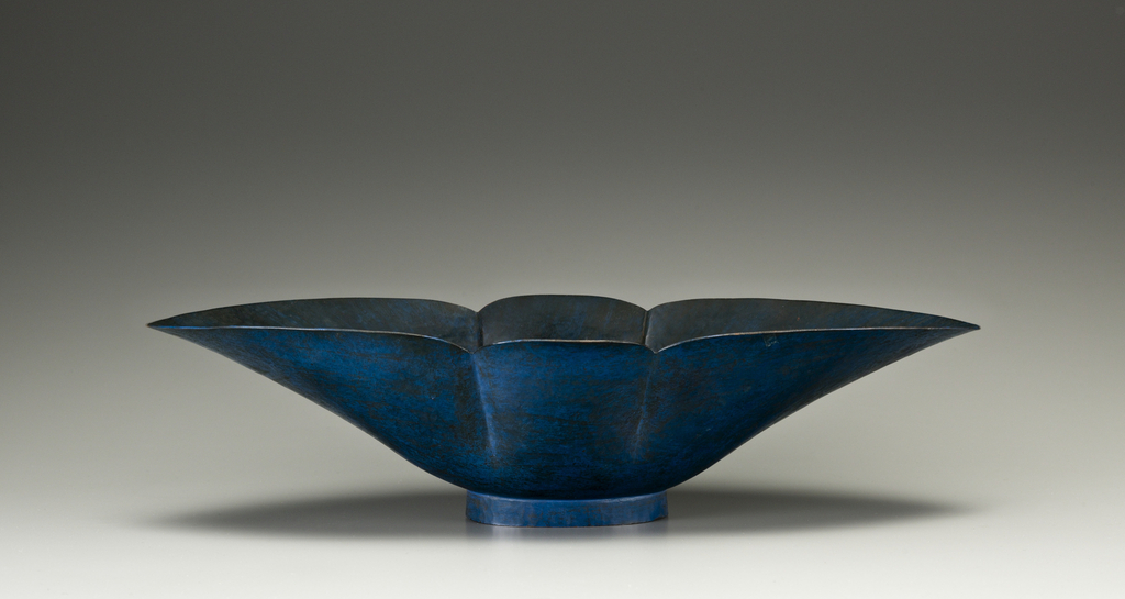 Blue painted copper bowl with wide, wing-like volume resting atop a circular foot.