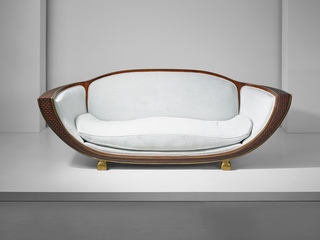 Gondola-shaped canapé constructed of carved Indian rosewood and veneer, brass and linen velvet and resting upon four swollen cubic brass feet. The piece's frame is covered with an illusionistic woven pattern outlined by brass, and its upholstery is a shimmering light blue-green hue.