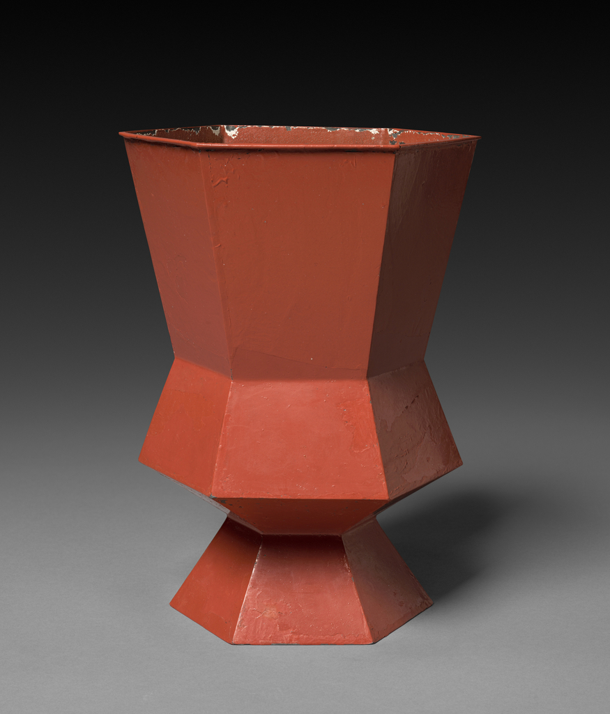 Hexagonal footed vase made up of zig-zagging tessellated, rust-colored panels.