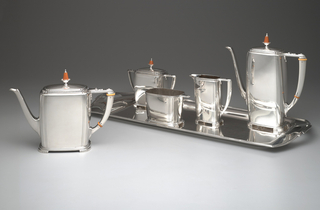 Silver tea and coffee service made up of six components; volumes rise up from stepped feet and boast minimal decoration save for incised lines and orange plastic finials and bands found on some of the angular bracket handles.