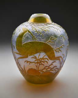 Translucent orange oval vase with depiction of leaping deer and stylized foliage and clouds set against iridescent silver-blue ground.
