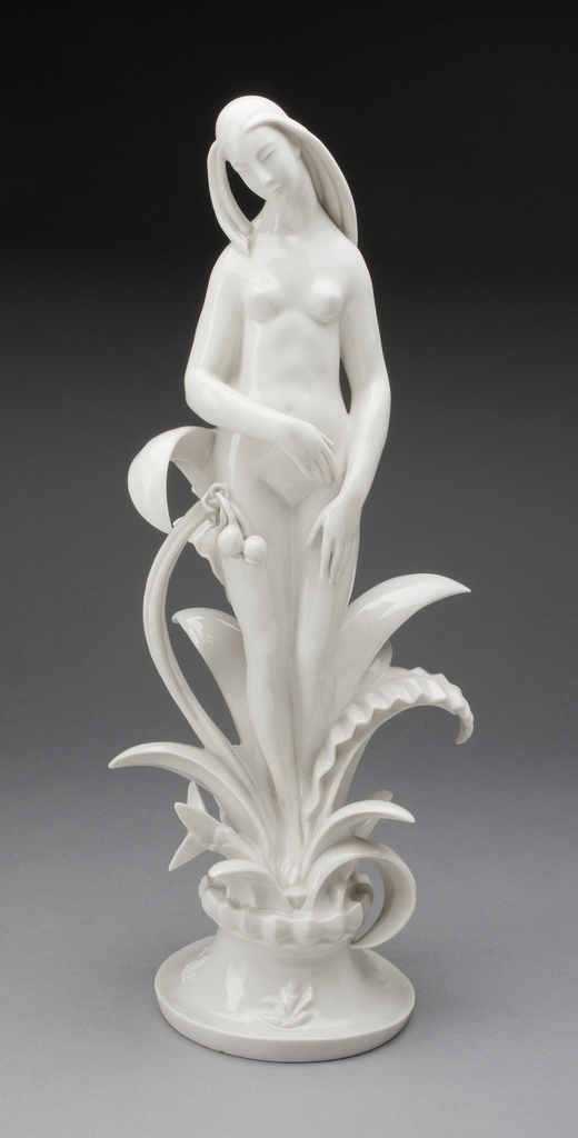 "Hard-paste porcelain allegorical figure of ""The Fruit""; nude female form stands among stylized fronds, grasses, and berries atop a conical base."