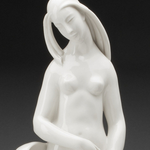 """Hard-paste porcelain allegorical figure of """"The Fruit""""; nude female form stands among stylized fronds, grasses, and berries atop a conical base."""