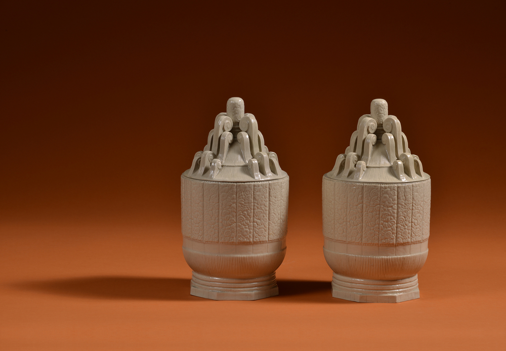 Pair of glazed ceramic covered urns whose bodies are made up of vertically incised foliate panels atop decorative bands of beads, flat planes, and fluting; lids comprised of series of inward-curling, fluted volutes that swell towards foliate finials.