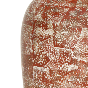 Tall, oval brass vase covered with a collage-like dappled pattern created by inlaid egg shell on a red lacquer ground; top culminates in shallow, black lip.