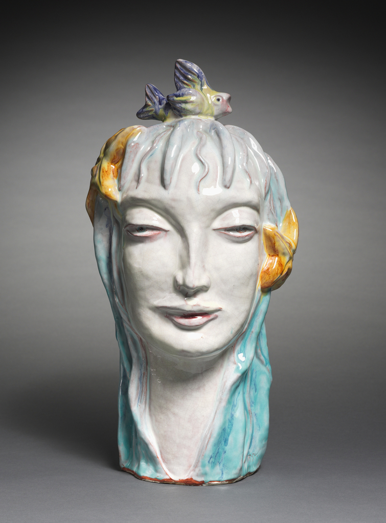 "Earthenware bust of the allegory of ""The Water""; figure's face and neck are glazed white while a turquoise hue spreads over her hair, which is ornamented by starfish and topped by a fish."