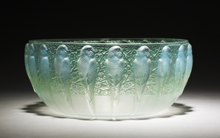 Iridescent, translucent bowl of blue-green hue with repeating pattern of parrots resting on branches of blossoms.