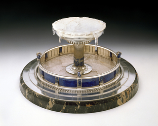 Round black marble base-stepped silver platform on top. Marble surmounted by a silver pool wall set with blue enamel plaques separated by short pilasters of lapis mounted in silver. Central fountain silver basin with vase; shaped fluted stem set with lapis panels and surmounted by rock crystal to simulate frozen water.