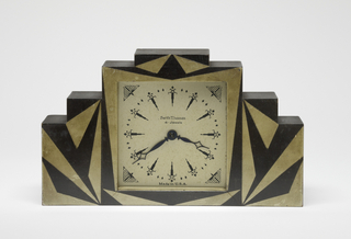 The Sutton wood mantle clock with rectangular wooden case, stepped sides, and geometric pattern of gold and black triangles painted on front around recessed square centered white face, and with square metal plate and winding key on back.