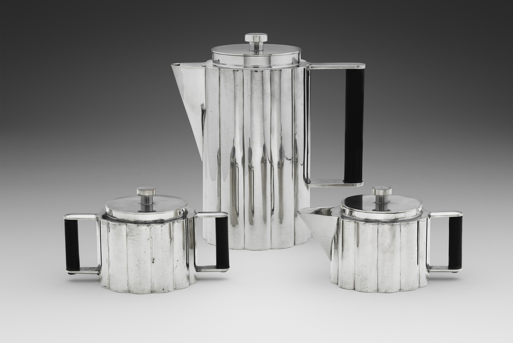 Three-piece handwrought pewter coffee set, each piece in cylindrical, vertically reeded form with removable lid, consisting of coffeepot with straight ebonized vertical wooden dowel handle; sugar bowl with two straight ebonized vertical wooden dowel handles; and creamer with straight ebonized vertical wooden   dowel handle.