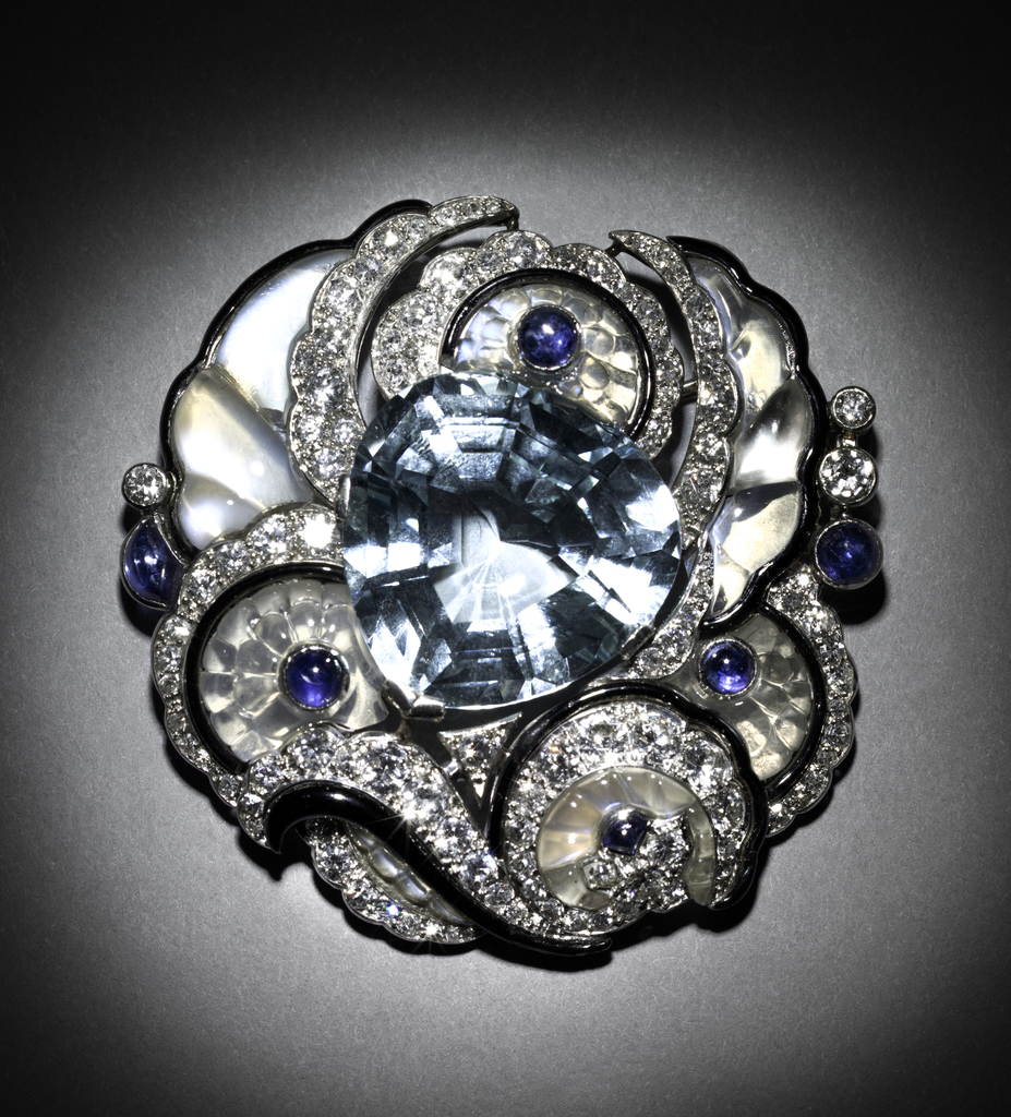 Openwork brooch consisting of a rounded triangular aquamarine stone set against swags and blossoms of carved moonstone, scalloped volutes of inset diamonds, and cabochon sapphire accents.