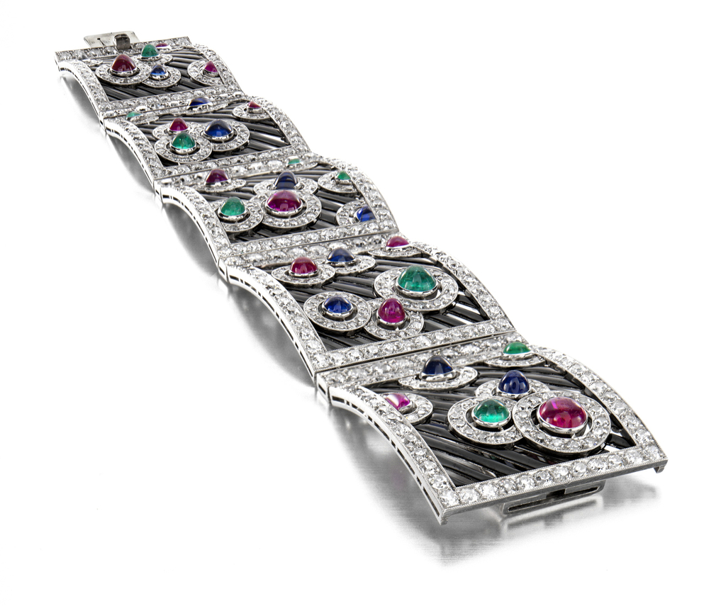 Bracelet comprised of five rectangular panels, each featuring different asymmetrical compositions of ruby, sapphire and emerald circles inscribed in diamonds against diagonal strips of black osmium.