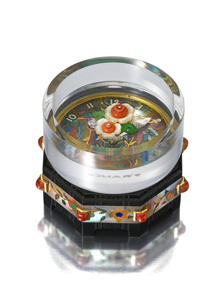 Clock comprised of rock crystal cylinder stacked atop a pagoda-inspired onyx base with floral decoration set into mother-of-pearl. Clock face boasts flattened scene of swimming koi with gem-encrusted fish-shaped hands emerging from two lotus blooms at center.