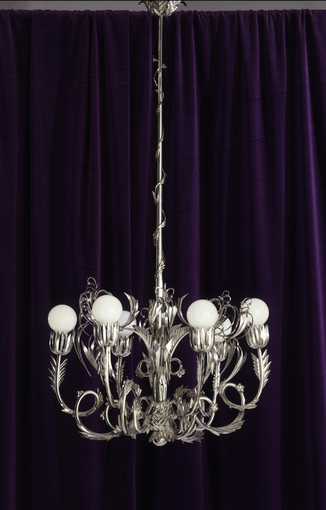 Highly reflective silvered bronze chandelier whose arms are twisting leafy branches capped with angular blossoms from which spherical light bulbs emerge; tendrils emerge from the light sockets and a solitary vine twists up the metal hanging rod, which terminates in a leaf-covered plate.