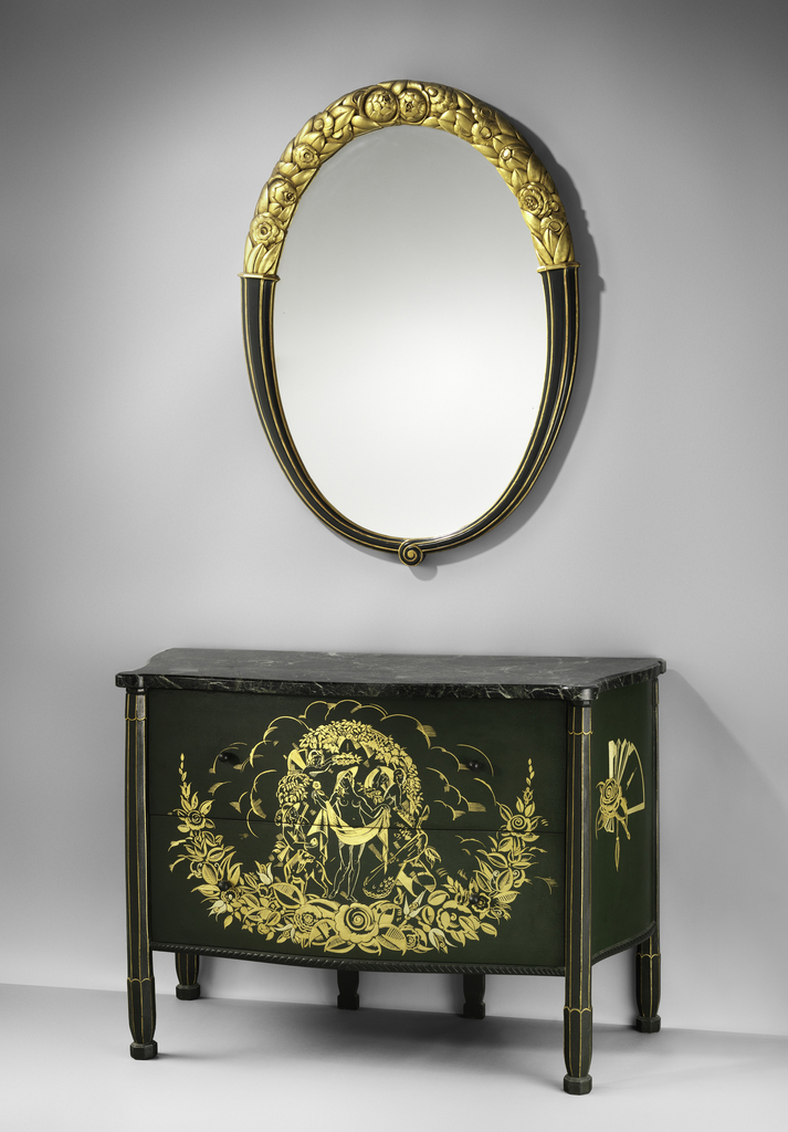 Ovoid mirror with painted and gold leafed cherry or pearwood frame; a stylized gilt floral swag rests atop the piece, springing from fluted horns that meet at bottom in a swirling accent.
