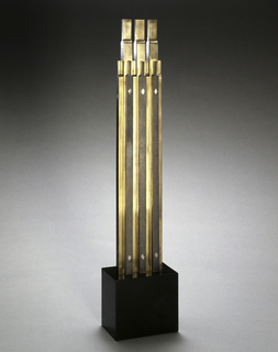 Metal and marble sculpture resembling a skyscraper.